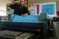 Farbwerk und Walze mit Papier werden über den Druckstock gerollt